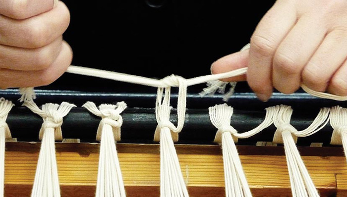 Tying warp onto a low loom